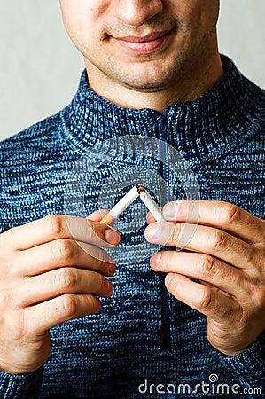 Male hands breaks cigarette