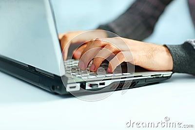 Male hands typing on laptop keyboard