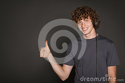 Male in headphones gesturing thumb up