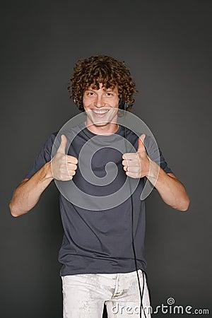 Male in headphones gesturing thumb ups