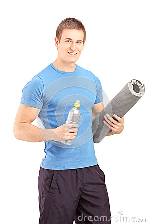 Male holding a bottle of refreshment drink and a mat after an ex