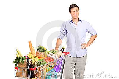 A male holding a shopping cart with groceries
