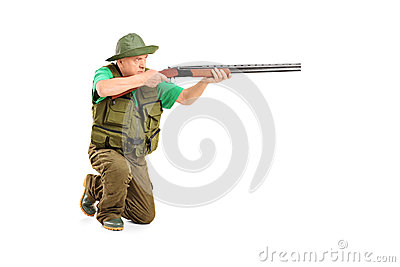 A male hunter shooting with a rifle