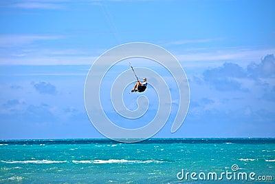 Male Kitesurfer grabing his board