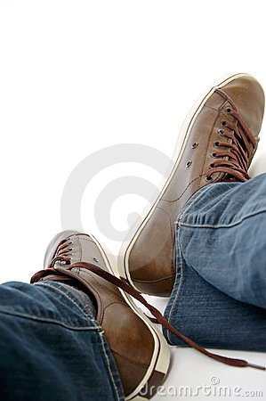 Male legs in brown shoes sneakers and jeans
