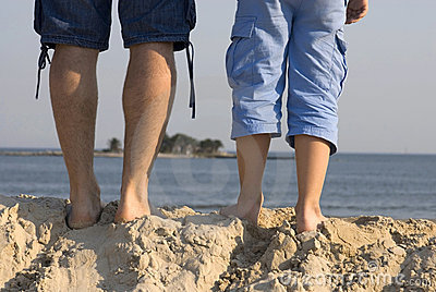 Male legs front of a beach