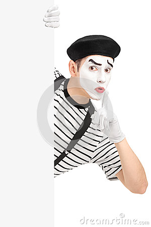 Male mime artist holding a blank panel and gesturing silence wit