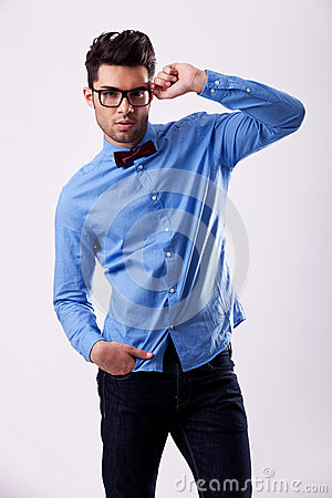 Male model wearing bow tie and holding his glasses
