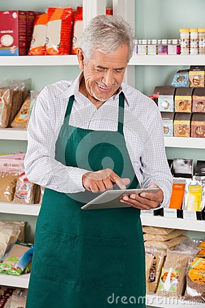 Male Owner Using Tablet In Supermarket