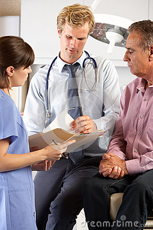Male Patient Being Examined By Doctor And Intern