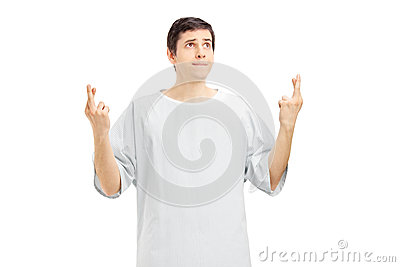 Male patient in a hospital gown with fingers crossed posing