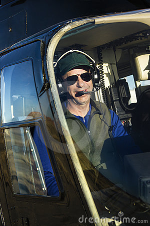 Male pilot in helicopter.