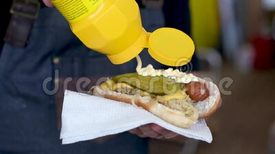 Male is pouring mustard on hot-dog stock footage