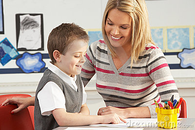 Male Primary School Pupil And Teacher Working