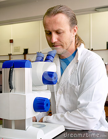 Male researcher in lab coat looks into microscope