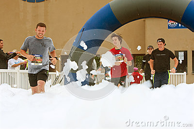 Male Runners Run Through Foam At Finish Line Of Race Editorial Photo