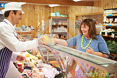 Male Sales Assistant Serving Customer In Delicatessen