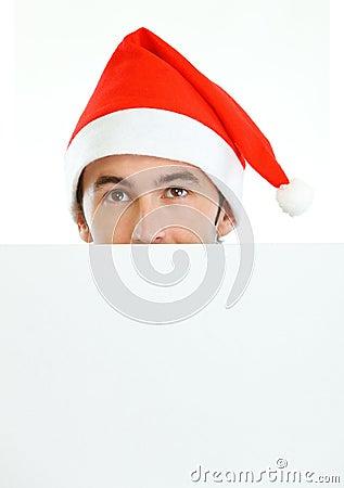 Male in Santas hat hiding behind blank billboard