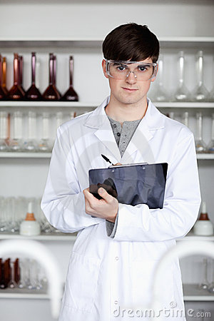 A male science student writing on a clipboard