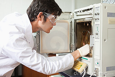 Male scientist using a laboratory chamber furnace