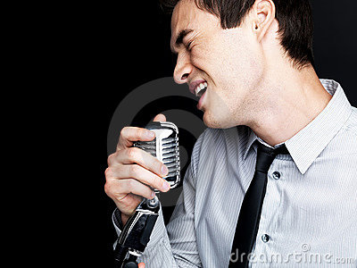 Male singer singing into old fashioned microphone
