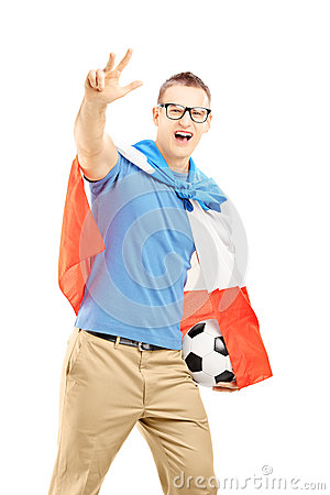 Male sport fan with flag of Holland holding a ball and gesturing