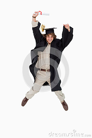Male student in graduate robe jumping