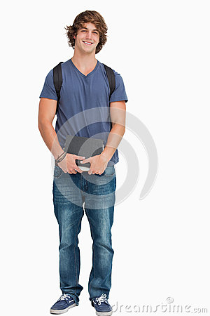 Male student posing with a backpack and books