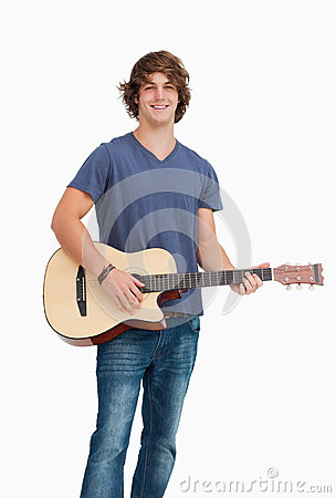 Male student posing while holding a guitar