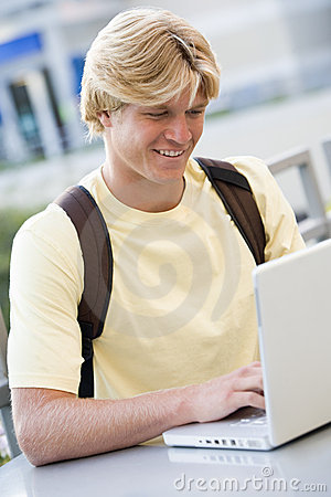 Male student using laptop outside
