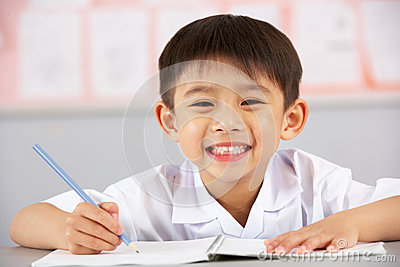 Male Student Working At Desk In Chinese School