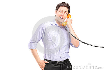 A male talking on a telephone