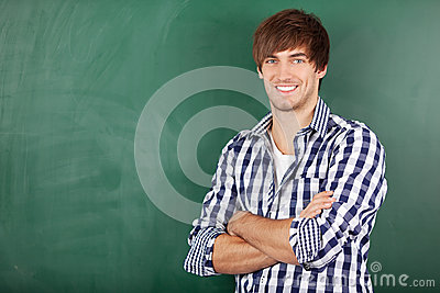 Male Teacher With Arms Crossed Standing Against Chalkboard