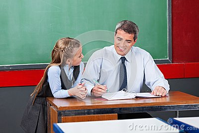 Male Teacher Explaining Lesson To Schoolgirl