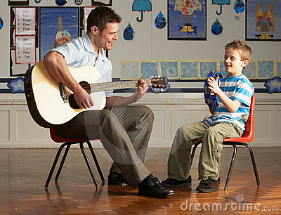 Male Teacher Playing Guitar With Pupil In Classroo