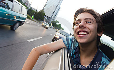 Male teenager in car enjoying city view