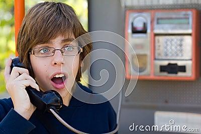 Male teenager talking on street phone