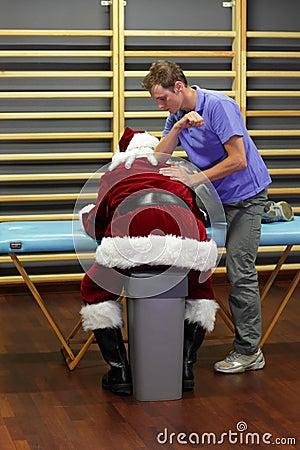 Male therapist massaging overworked Santa Claus