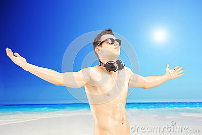 Male tourist with speakerphones spreading his arms, next to a se