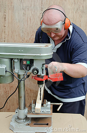 Male using a drill press on wood