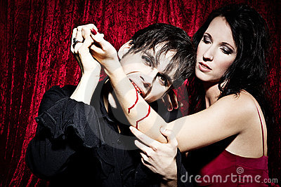 Male vampire is biting a woman