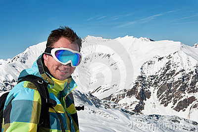 Male wearing goggles and ski jacket smiling