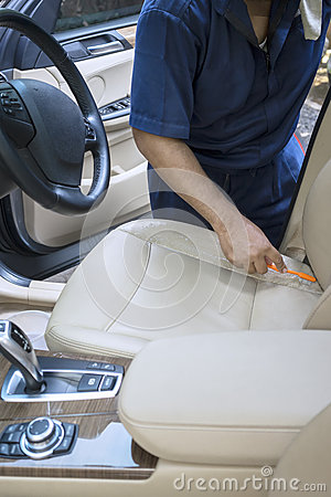 Free Male Worker Scrubbing The Car Seat Stock Image - 69671801