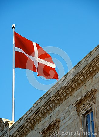 Maltese flag close up on the roof of building, malta flag in blue sky background, fragment, flag on windy day, read and white flag