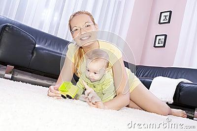Mamã bonita com seu filho que joga feliz.