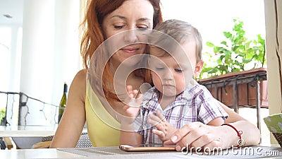 Mamã com uso do filho um smartphone para o Internet video estoque