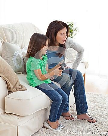 Mamã concentrada e filha que jogam os jogos video