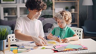 Mamã criativa da família e criança pequena que fazem colagens com papel, tesouras e colagem video estoque