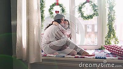 Mamãe e filha estão sentados na janela sobre decorações de Natal família feliz mãe e bebê vídeos de arquivo