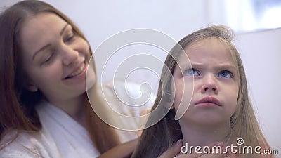 Mamãe escova suavemente o cabelo da sua filha video estoque